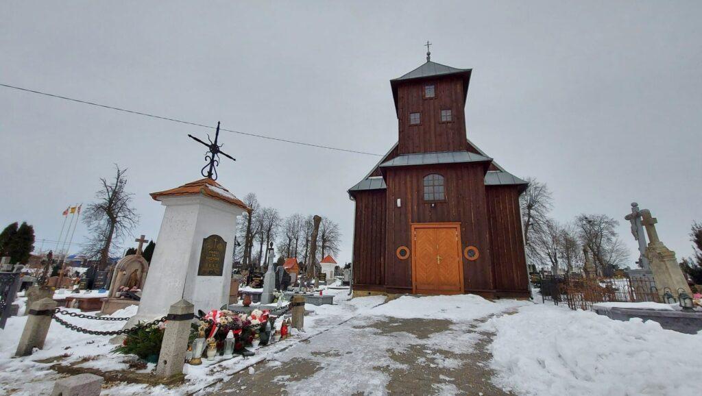 Zdjęcie przedstawia Pomnik poświęcony siemiatyckim Powstąńcom Styczniowym z 1863 roku - w tle drewniana kaplica Św. Anny